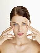 Woman massaging her under-eye area