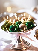 Shiny Christmas bauble candles on a silver stand