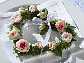Heart-shaped wreath of roses on embroidered napkin