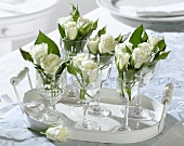 White roses in wine glasses on a tray