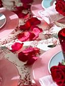 Rote Rosenblütenblätter als Tischdekoration
