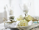 Two windlights and place-setting with white rose