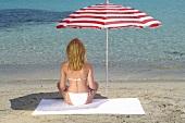Frau sitzt am Strand unter Sonnenschirm