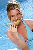 Frau beisst in ein Stück Honigmelone am Swimmingpool