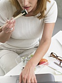 Woman eating sushi at her desk