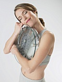 Woman hugging bathroom scales