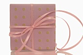 Gift in spotted gift wrapping paper with pink ribbon