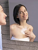 Woman in front of mirror putting cream on her chest