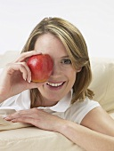 Woman holding an apple in front of her eye
