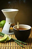 Aroma lamp, bowl of tea and limes