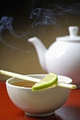 Teapot and bowl of tea with a slice of lime