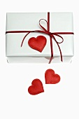 Gift in white wrapping paper with red heart