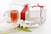 White gifts with red bows on plate, glass of sparkling wine