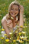 Frau hockt auf einer Wiese und hält eine Blume