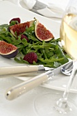Rocket with figs and raspberries, glass of white wine