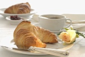 Breakfast place-setting with croissant and rose