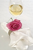 Glass of white wine and napkin with pink rose