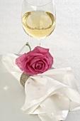 Weissweinglas und Serviette mit pinkfarbener Rose