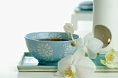 Bowl of tea with sugar swizzle stick, aroma lamp, orchids
