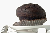 Chocolate muffin in paper case, fork beside it
