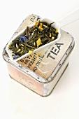 Tea tin and small porcelain scoop containing tea mixture