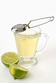 Tea infuser, glass cup of tea and lime halves