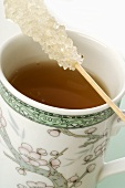 Mug of tea with sugar swizzle stick (close-up)
