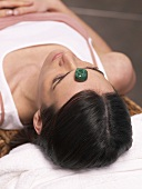 Woman lying down with a healing stone on her forehead