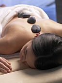 Woman having a warm stone massage
