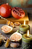 Pomegranates, figs and dates, two candles