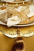 Christmas place-setting with white napkin and gold bow
