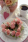 Heart-shaped wreath of roses on plate, cup of coffee
