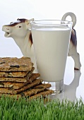 Glass of milk, pumpkin seed crispbread and pottery cow