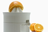 Electric citrus squeezer with oranges