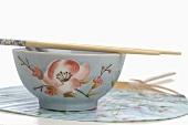 Asian bowl with chopsticks on fan