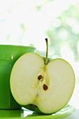 Half an apple and green beaker