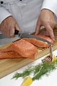 Chef cutting salmon