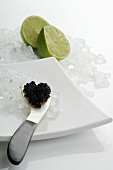 Caviar on mother-of-pearl spoon, crushed ice, lime halves