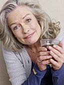 Ältere Frau mit einem Glas Tee