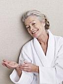 Ältere Frau im Bademantel mit Tabletten
