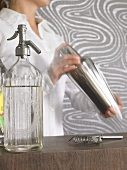 Woman mixing drink in cocktail shaker, soda syphon, bar strainer