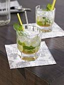 Two Mojitos on wooden table (close-up)