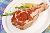 Raw lamb chop on a plate, rosemary, lemon