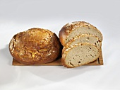 Loaves of bread, whole & partly sliced, on a wooden board
