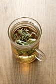 A glass cup of sage tea with sage leaves