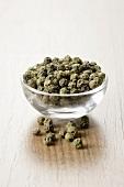 Green peppercorns in a small glass dish