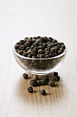 Black peppercorns in a small glass dish