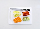 Julienne vegetables on a chopping board with a knife