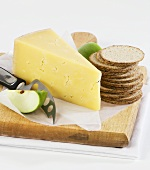 Piece of cheese with crackers and apple on a wooden board