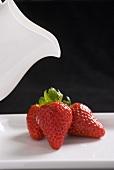 Three fresh strawberries with a cream jug